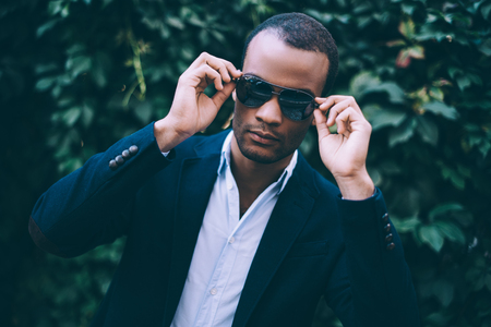 Confident in his perfect style. Handsome young African man in smart casual wear adjusting his sunglasses and looking at camera while standing against green plant background outdoors