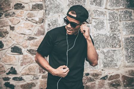 stoned: Enjoying his favorite music. Handsome young African man in headphones singing and gesturing while standing against the stoned wall outdoors
