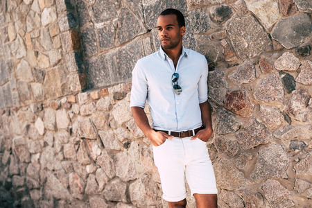 metrosexual: Casually handsome. Handsome young African man in smart casual clothes holding hands in pockets and looking away while standing against the stoned wall outdoors