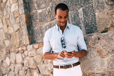 Enjoying his favorite music. Handsome young African man in headphones carrying smart phone and looking at it with smile while standing against the stoned wall outdoors