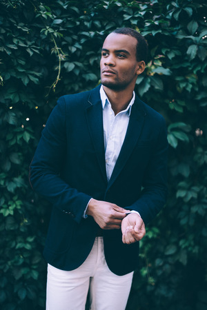 metrosexual: Used to look perfect. Handsome young African man in smart casual wear adjusting his sleeve and looking away while standing against green plant background outdoors