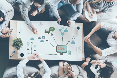 Discussing new strategy. Top view of business people discussing something while sitting around the desk together and pointing large paper with conceptual business icons drawn on it photo