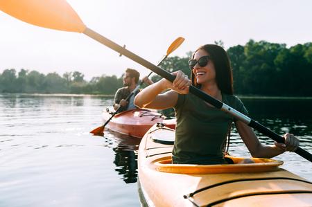 카약 타기 좋은 날. 아름 다운 젊은 부부 함께 호수에 카약과 미소 스톡 콘텐츠