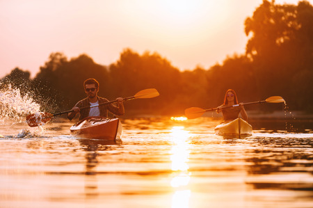 water splashing: Couple kayaking together. Confident young couple kayaking on river together with sunset in the backgrounds Stock Photo