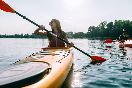 recreational: Ready for adventures. Beautiful young smiling couple kayaking on lake together