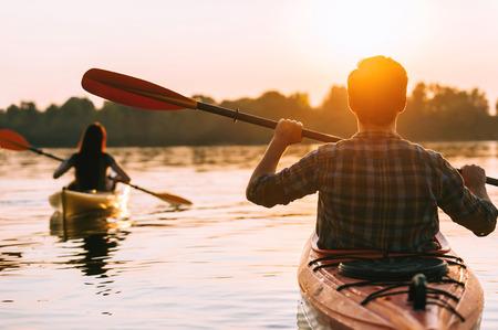 Bijeenkomst zonsondergang op kajaks. Achtermening van het mooie jonge paar kayaking op meer samen met zonsondergang op de achtergrond