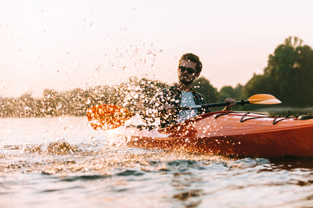 Spending great time on water. Handsome young man kayaking on lake with sunset in the background
