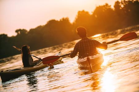 最高の夕日を一緒に会議。若いカップルは、背景の夕日と湖でカヤックの背面図