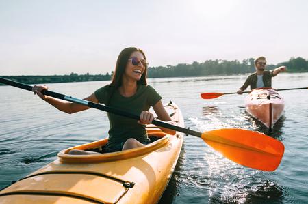Coppia, kayak, insieme Belle giovani coppie che kayaking sul lago insieme e sul sorridere Archivio Fotografico - 64179249