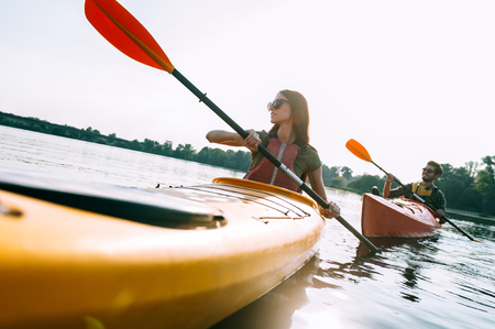 recreational: Couple kayaking. Beautiful young couple kayaking on lake together and smiling