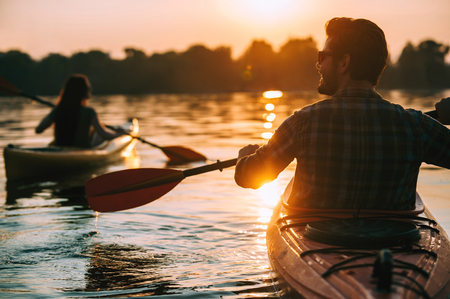 Meeting sunset on kayaks. Rear view of young couple kayaking on lake together with sunset in the backgrounds Zdjęcie Seryjne