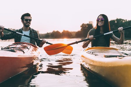 recreational: Life is better on the river. Cheerful young couple kayaking on river together with sunset in the backgrounds