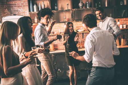 Party that never ends. Cheerful young people dancing and drinking while enjoying home party on the kitchen