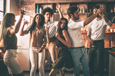 Party time! Cheerful young people dancing and drinking while enjoying home party on the kitchen