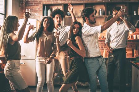 파티 타임! 부엌에서 집에 파티를 즐기면서 춤과 술을 마시는 쾌활한 젊은 사람들