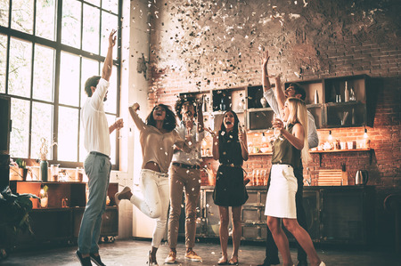 Just having fun. Full length of cheerful young people throwing confetti and jumping while enjoying home party on the kitchen Stockfoto