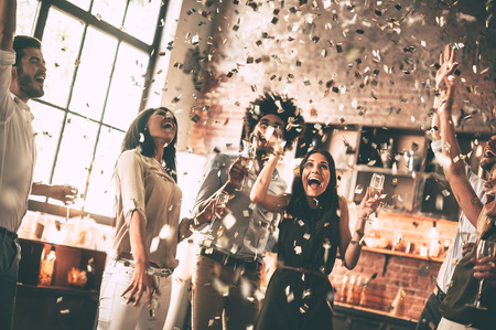 dinner party: Enjoying bright moments. Cheerful young people throwing confetti and smiling while enjoying home party on the kitchen Stock Photo