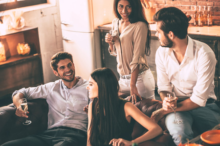 dinner party: Friends will be friends. Cheerful young people enjoying food and drinks while spending nice time in cofortable chairs at home together Stock Photo