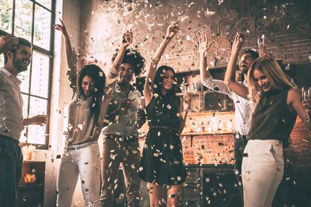 멋진 파티 즐기기. 색종이를 던지고 부엌에 집에 파티를 즐기면서 점프하는 행복 젊은 사람들의 그룹 스톡 콘텐츠