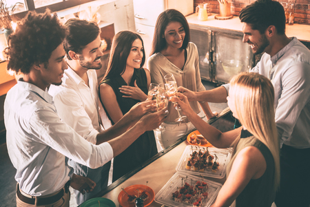 dinner party: Cheers to old friends! Top view of cheerful young people cheering with champagne flutes and looking happy while having party on the kitchen Stock Photo