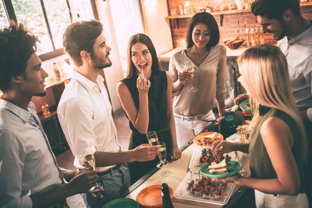 A l'occasion d'une fête à la maison. Un groupe de jeunes joyeux jouissant d'une fête à la maison avec des collations et des boissons en communiquant avec la cuisine