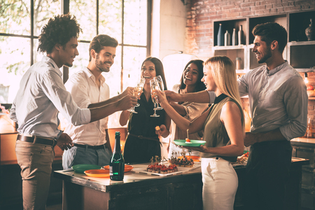 Celebration with nearest friends. Group of cheerful young people cheering with champagne flutes and looking happy while having party on the kitchen