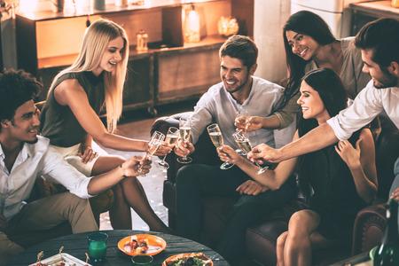 친구에게 건배! 함께 부엌에 cofortable 의자에서 좋은 시간을 보내는 동안 음식과 음료를 즐기는 쾌활한 젊은 사람들이 스톡 콘텐츠