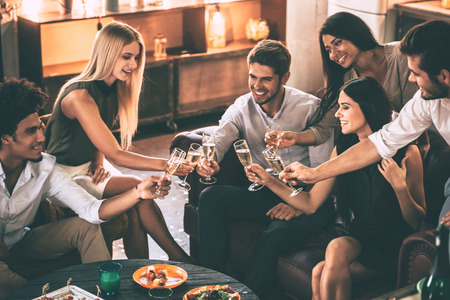 Cheers to friends! Cheerful young people enjoying food and drinks while spending nice time in cofortable chairs on the kitchen together