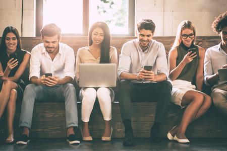 Digitaal leven. Vooraanzicht van jongeren die verschillende gadgets gebruiken, terwijl ze dicht bij elkaar in de rij zitten Stockfoto