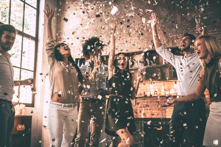 Confetti plezier. Groep gelukkige jonge mensen het gooien van confetti en springen terwijl u geniet van home party op de keukentafel