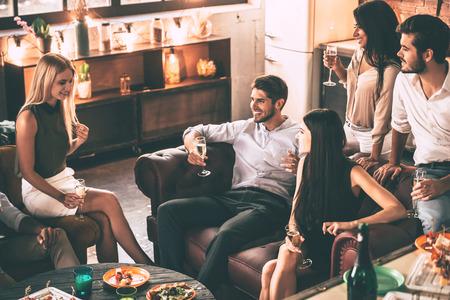 Tiempo despreocupado con los amigos. Vista superior de los jóvenes alegres disfrutando de la comida y bebidas mientras pasa tiempo agradable en cómodas sillas en casa juntos