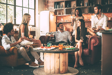 dinner party: Enjoying time with best friends. Group of cheerful young people enjoying food and drinks while spending nice time in cofortable chairs on the kitchen together Stock Photo