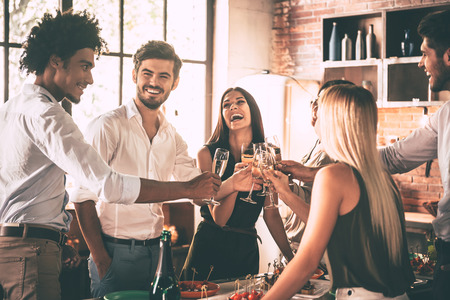 social gathering: Meeting with old friends. Cheerful young people cheering with champagne flutes and looking happy while having home party