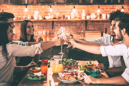 dinner party: Cheers to friends! Group of cheerful young people cheering with champagne flutes and looking happy while while sitting at the dinning table together Stock Photo