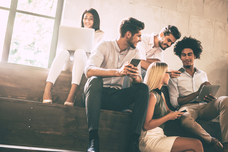 students group: Digital age students. Group of cheerful young people communicting while holding different gadgets and sitting close to each other on steps Stock Photo