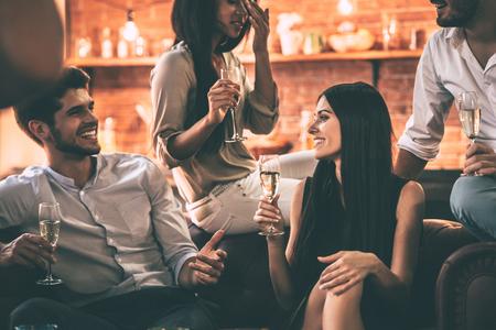 Onbezorgde tijd met beste vrienden. Groep vrolijke jongeren die van voedsel en dranken genieten terwijl thuis het doorbrengen van aardige tijd in cofortable stoelen