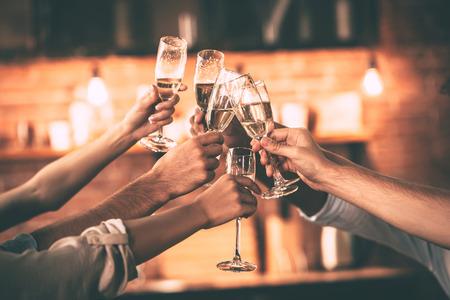 flauta: ¡Aclamaciones! Grupo de personas animando con copas de champán con el interior de la casa en el fondo Foto de archivo