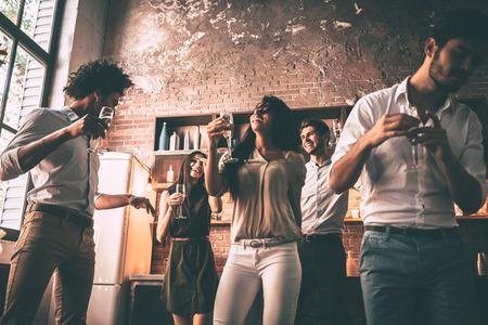 Il suffit de danser! Faible angle de vue de jeunes joyeux qui dansent et boivent en profitant d'une fête à la maison dans la cuisine