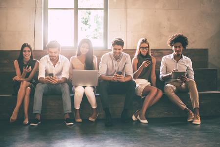Moderne studenten. Vooraanzicht van jongeren met verschillende gadgets zittend dicht bij elkaar in een rij Stockfoto