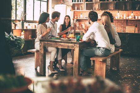 Gustare la cena con gli amici. Gruppo di giovani allegri gustare la cena, mentre seduto sulla cucina insieme