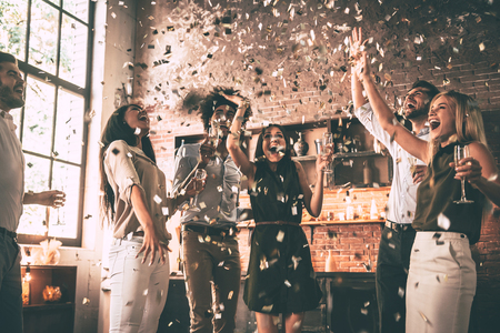 Enjoying bright moments. Group of happy young people throwing confetti and jumping while enjoying home party on the kitchen