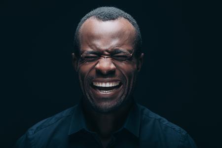 Einen Gesicht machen . Porträt des jungen afrikanischen Mannes , der ein Gesicht macht , während Augen geschlossen und vor schwarzem Hintergrund