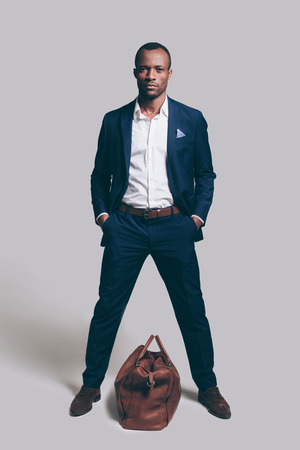 Me and my bag. Full length of handsome young African man in full suit holding hands in pockets and looking at camera while standing against grey background with brown leather bag laying near him Stock Photo