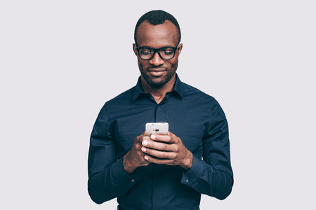 african business man: Typing business message. Handsome young African man holding smart phone and looking at it while standing against grey background