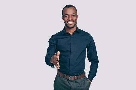 shaking out: Welcome on board! Handsome young African man stretching out hand for shaking and smiling to you while standing against grey background