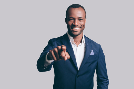 black male: I choose you! Handsome young African man in smart casual jacket pointing you and smiling while standing against grey background