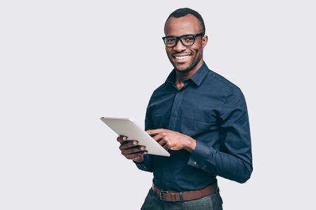 Hoe kan ik u helpen? Knappe jonge Afrikaanse mens die digitale tablet houdt en camera met glimlach bekijkt terwijl status tegen grijze achtergrond