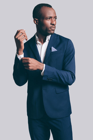 male fashion model: Perfect style. Handsome young African man in full suit adjusting his  sleeve and looking away while standing against grey background