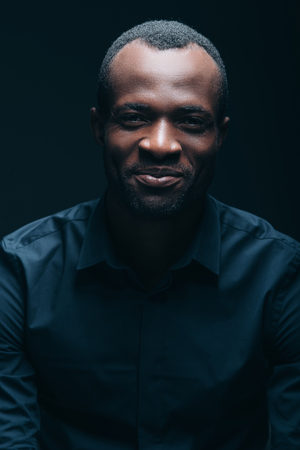 toothless: Always stay real! Portrait of handsome young African man looking at camera with smile while being in front of black background