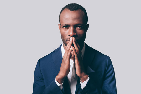 masculinity: Elegance and masculinity. Portrait of thoughtful young African man in smart casual jacket holding hand clasped near face and looking at camera while standing against grey background Stock Photo